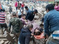 Handout picture released by the Colombian Army press office showing people helping to carry a woman after mudslides following heavy rains, in Mocoa, Putumayo department, on April 1, 2017.