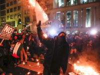 Protesters burn signs outside the National Press Building ahead of the presidential inauguration, Thursday, Jan. 19, 2017, in Washington. (AP Photo/John Minchillo)